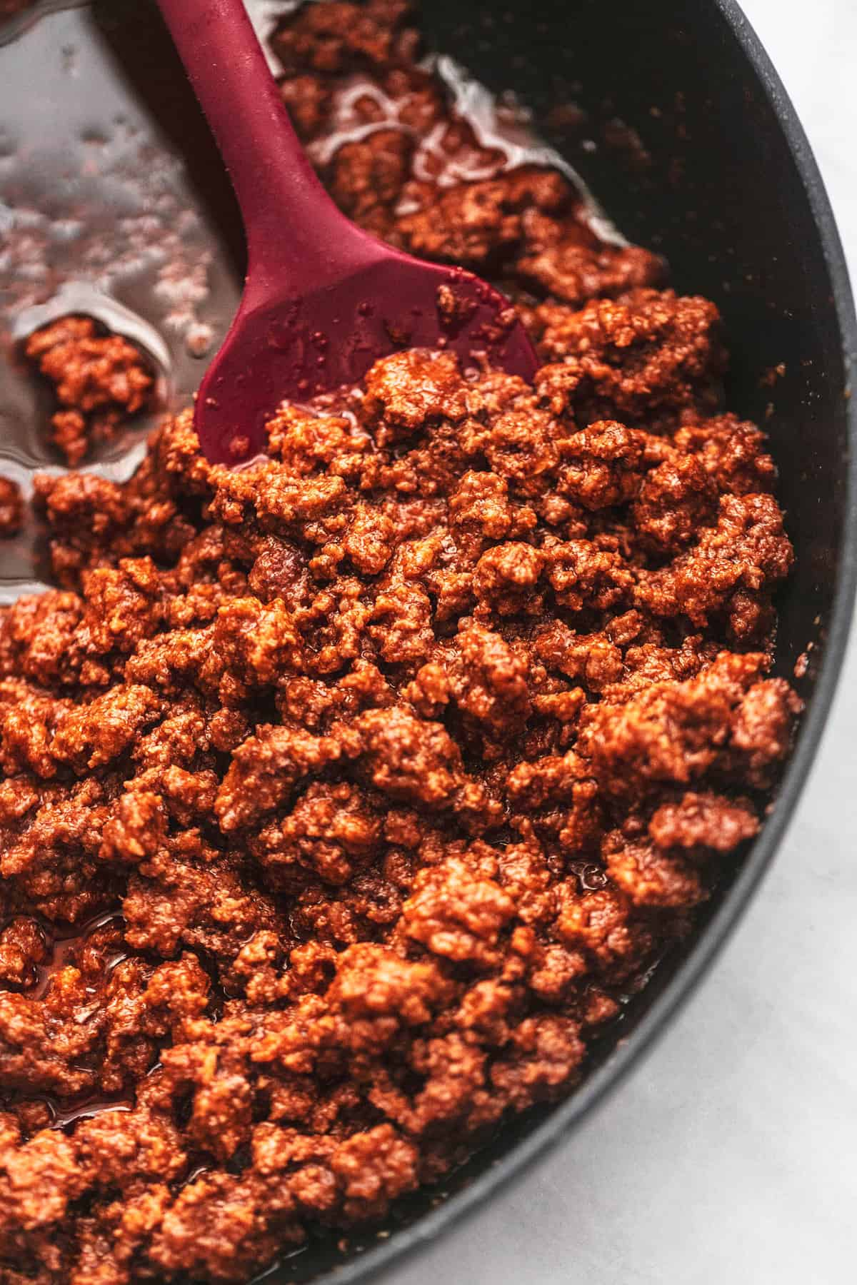 close up top view of ground beef with a spatula in a pan.