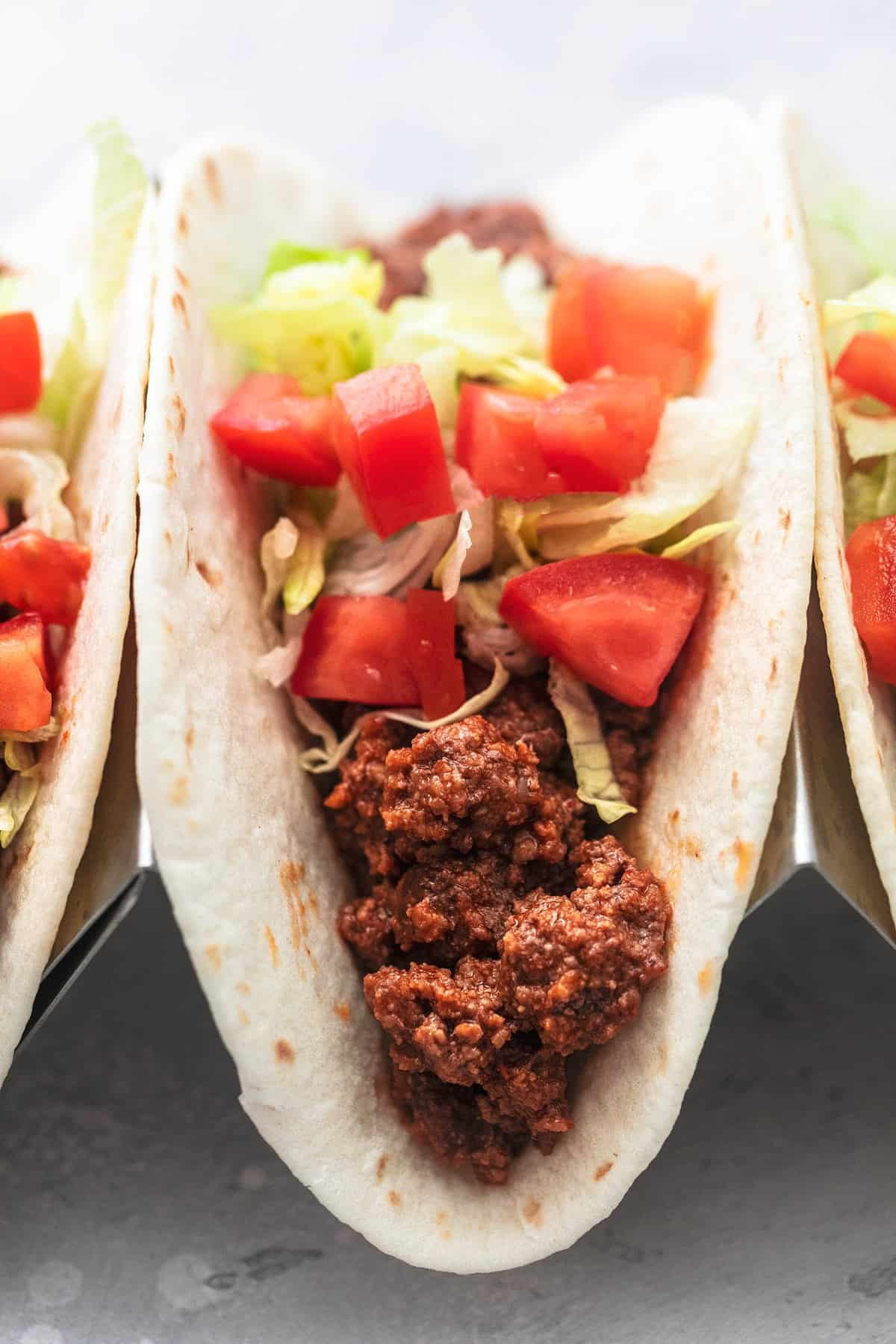 close up of a ground beef taco with toppings in a taco holder with more tacos on the sides.
