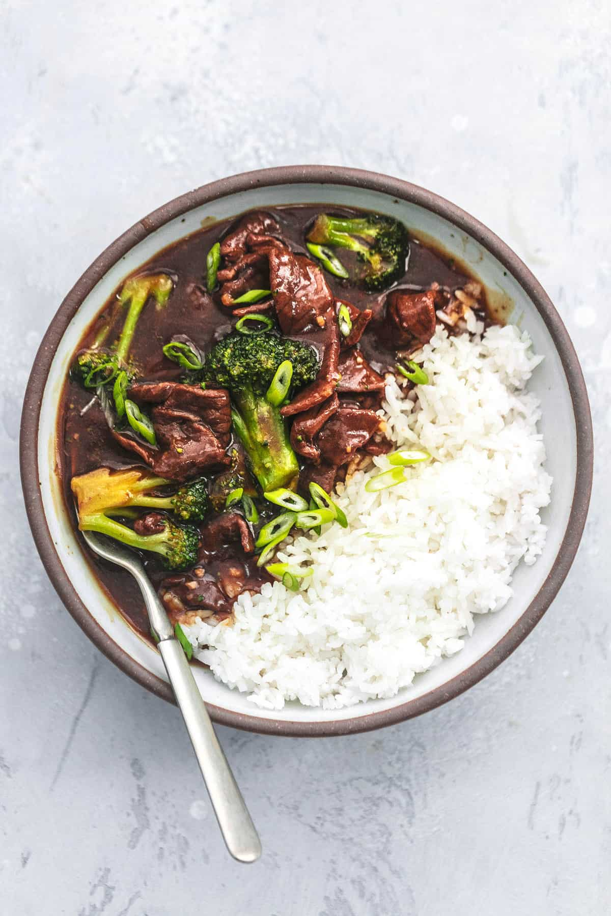 chinese beef and broccoli in bowl with fork