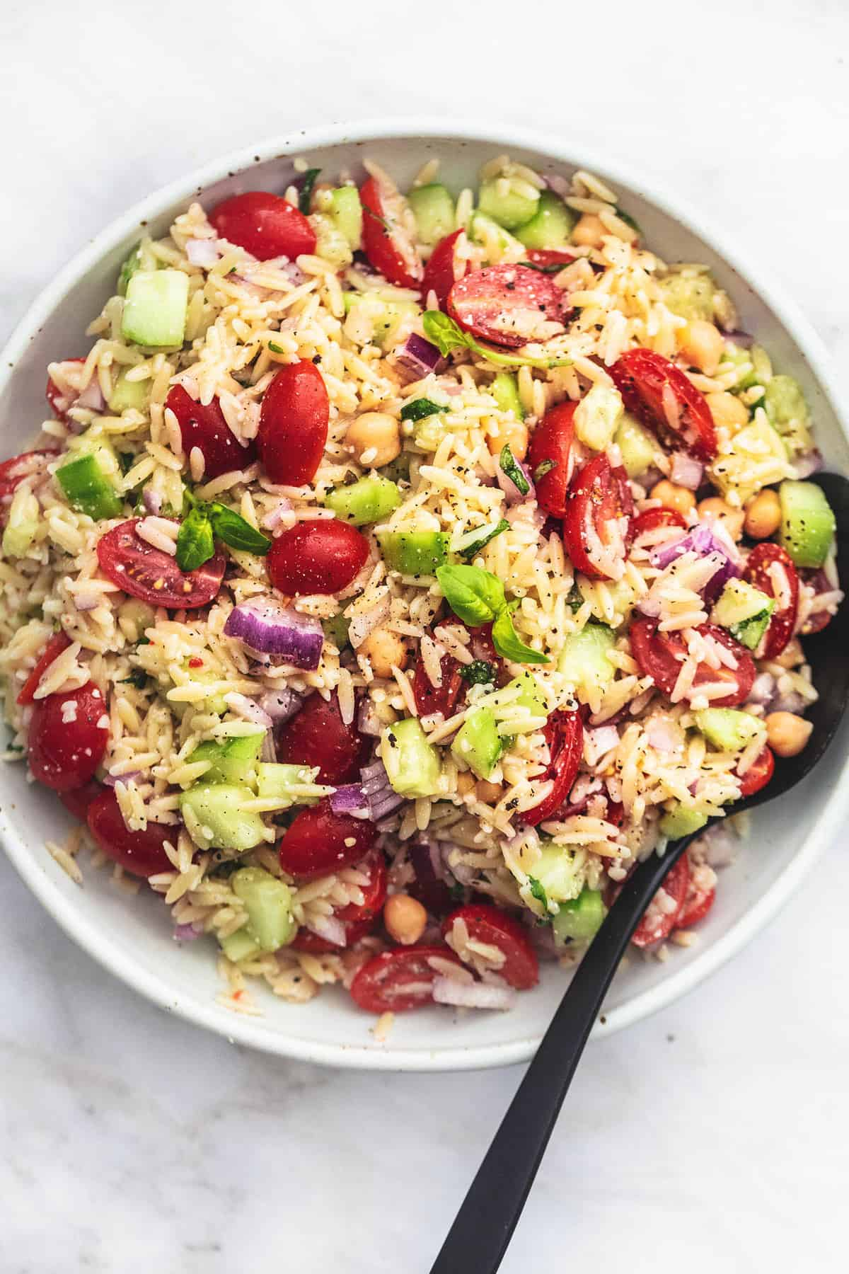 top view of Italian orzo salad with a serving spoon in a bowl.