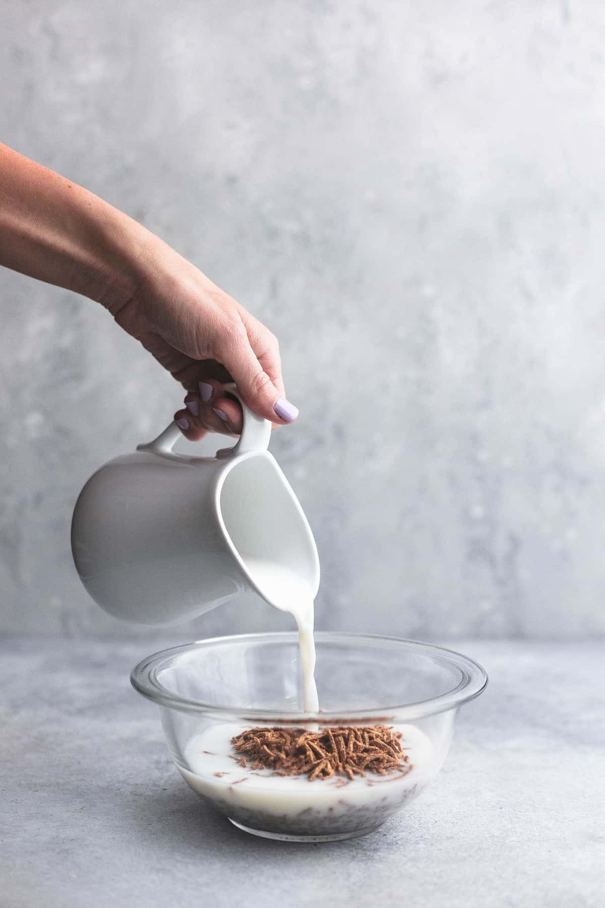 Milk is poured into a bowl of bran cereal