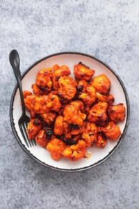 buffalo cauliflower on a white plate with a black fork on a gray table