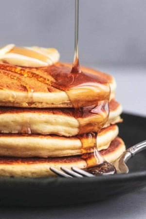 up close syrup pouring onto stack of pancakes on a plate with a fork