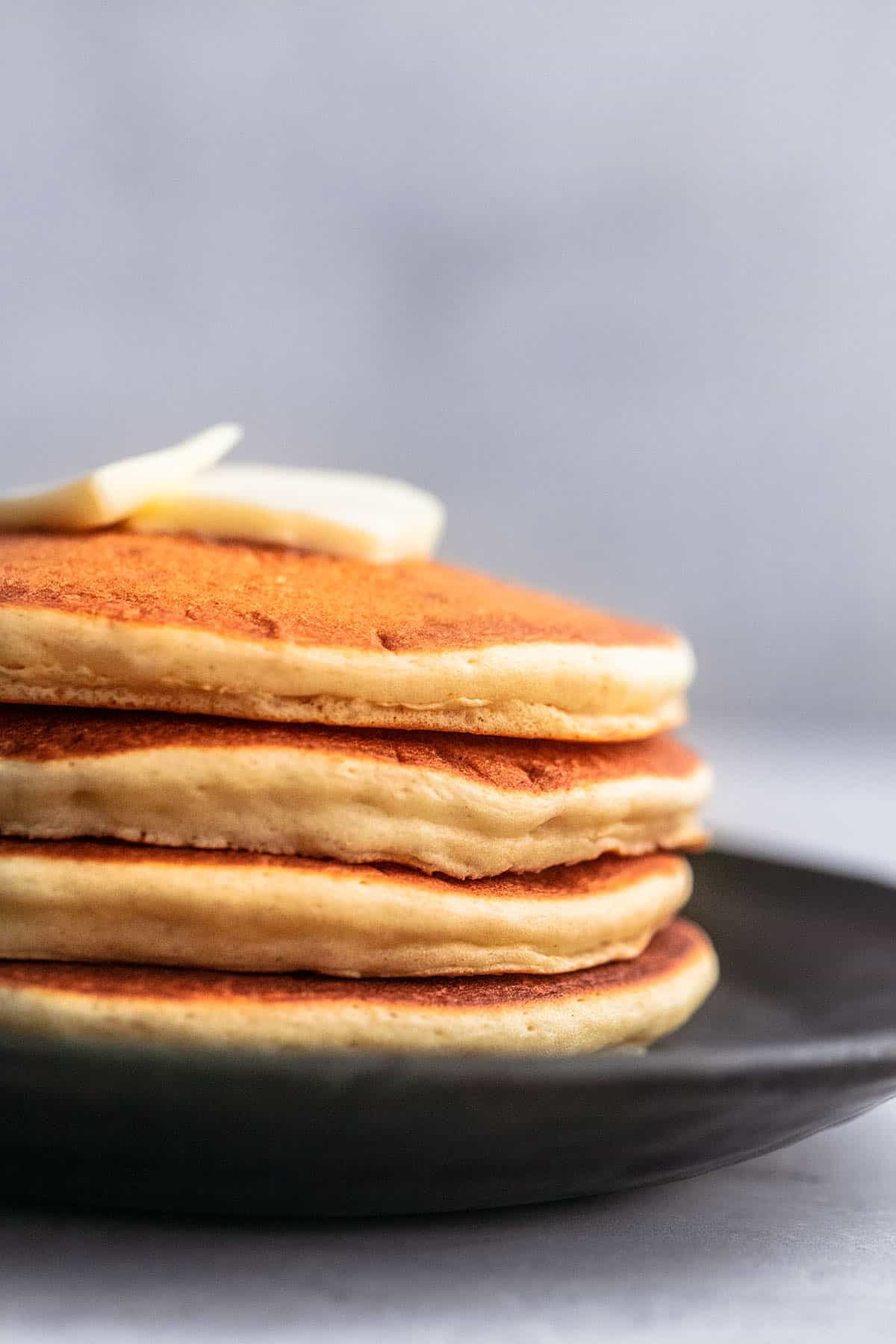 butter on top of a stack of pancakes on a plate
