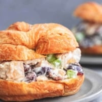 up close chicken salad sandwich croissant on a plate