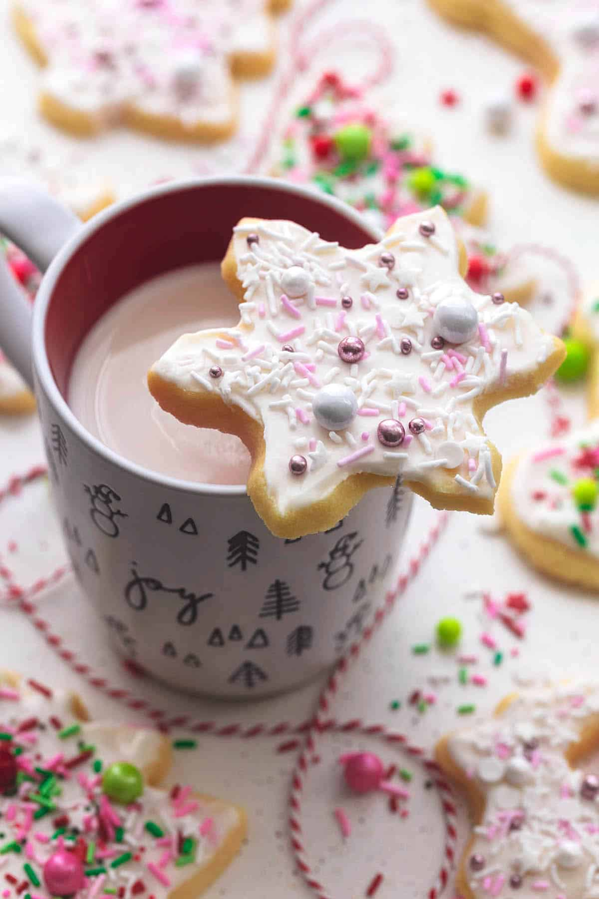 snowflake shaped sugar cookie with sprinkles resting on top of hot cocoa mug