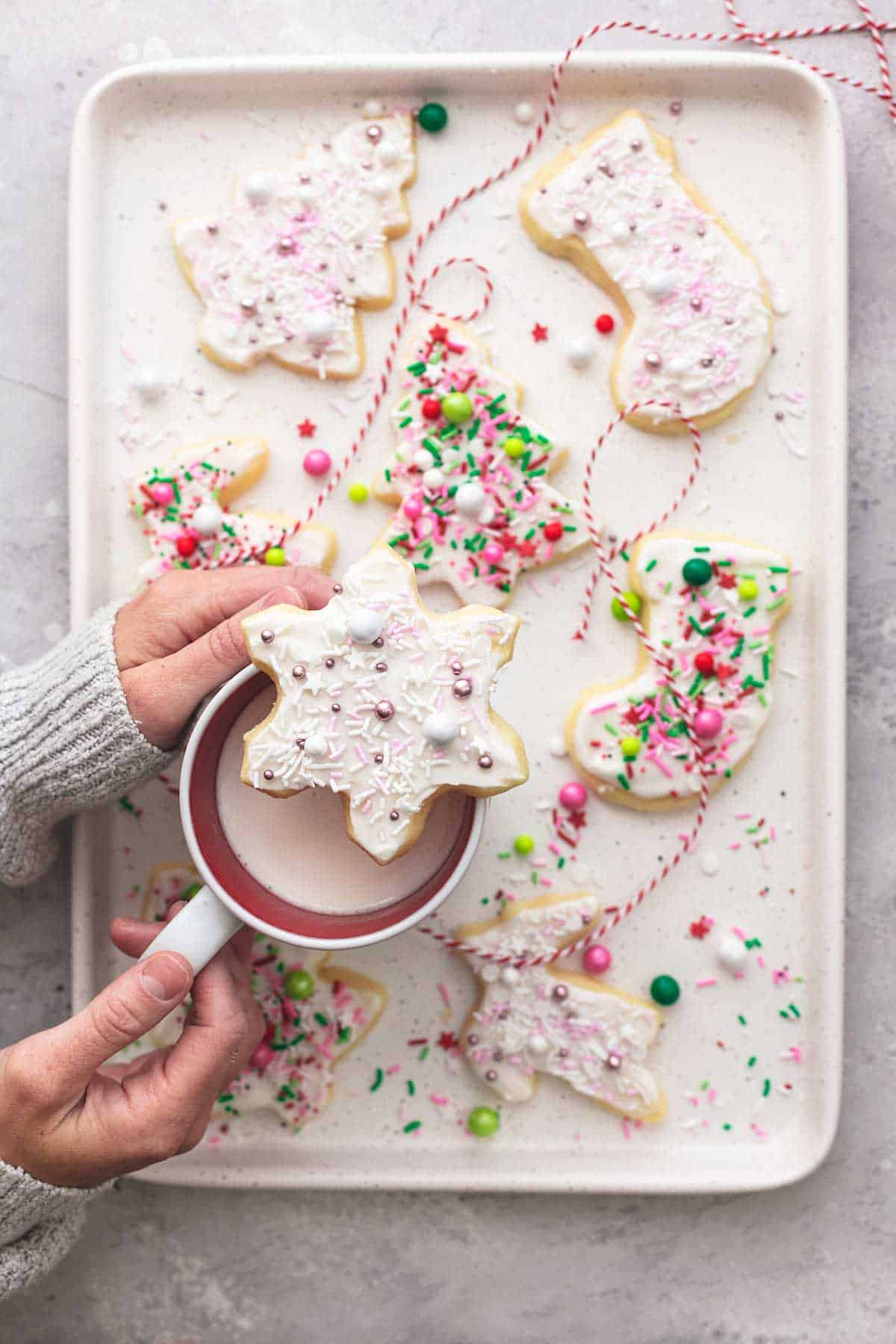 overhead view of hands holding mug of hot chocolate on a tray with sugar cookies