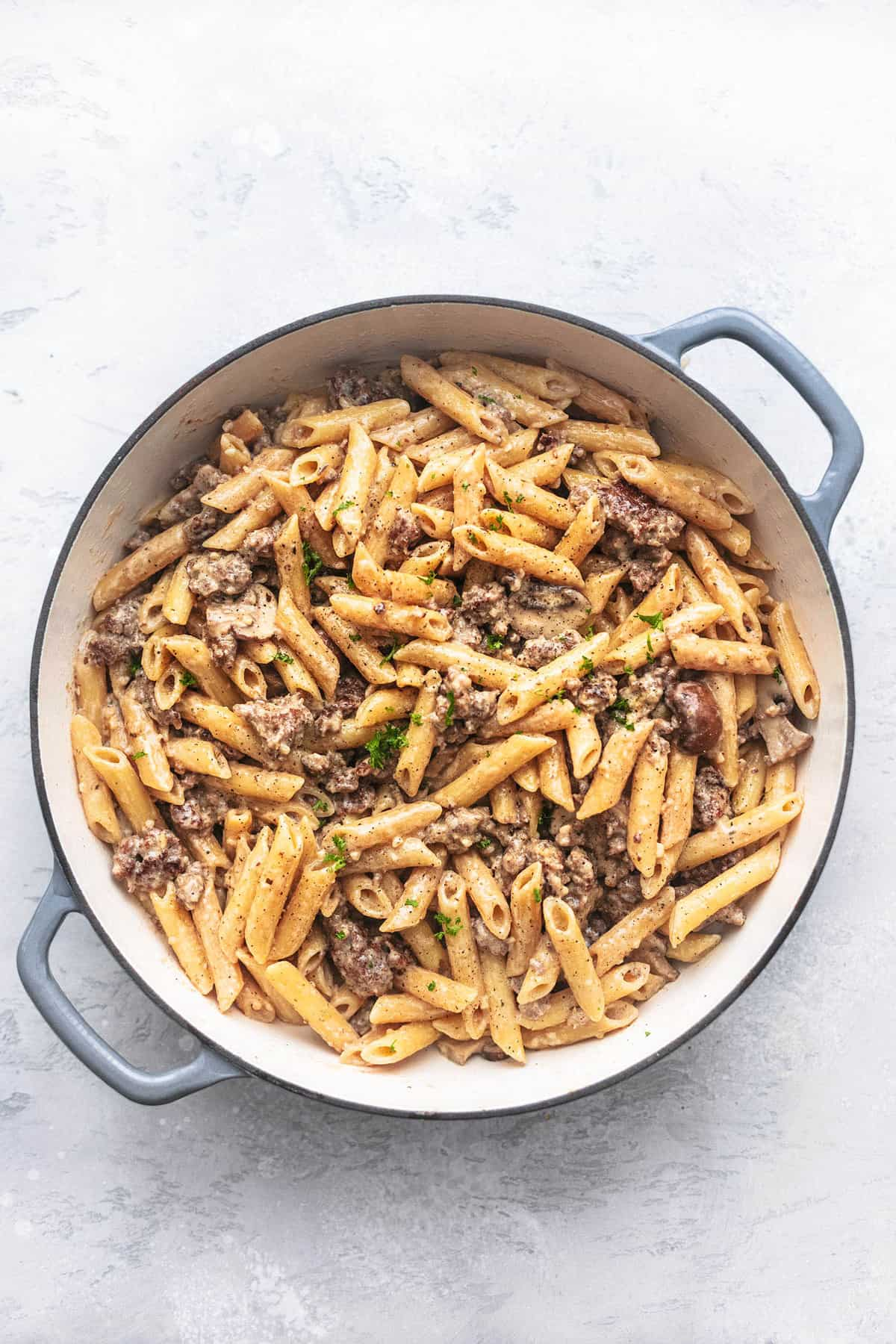 penne with white sauce and mushrooms and ground pork in a skillet on a gray background
