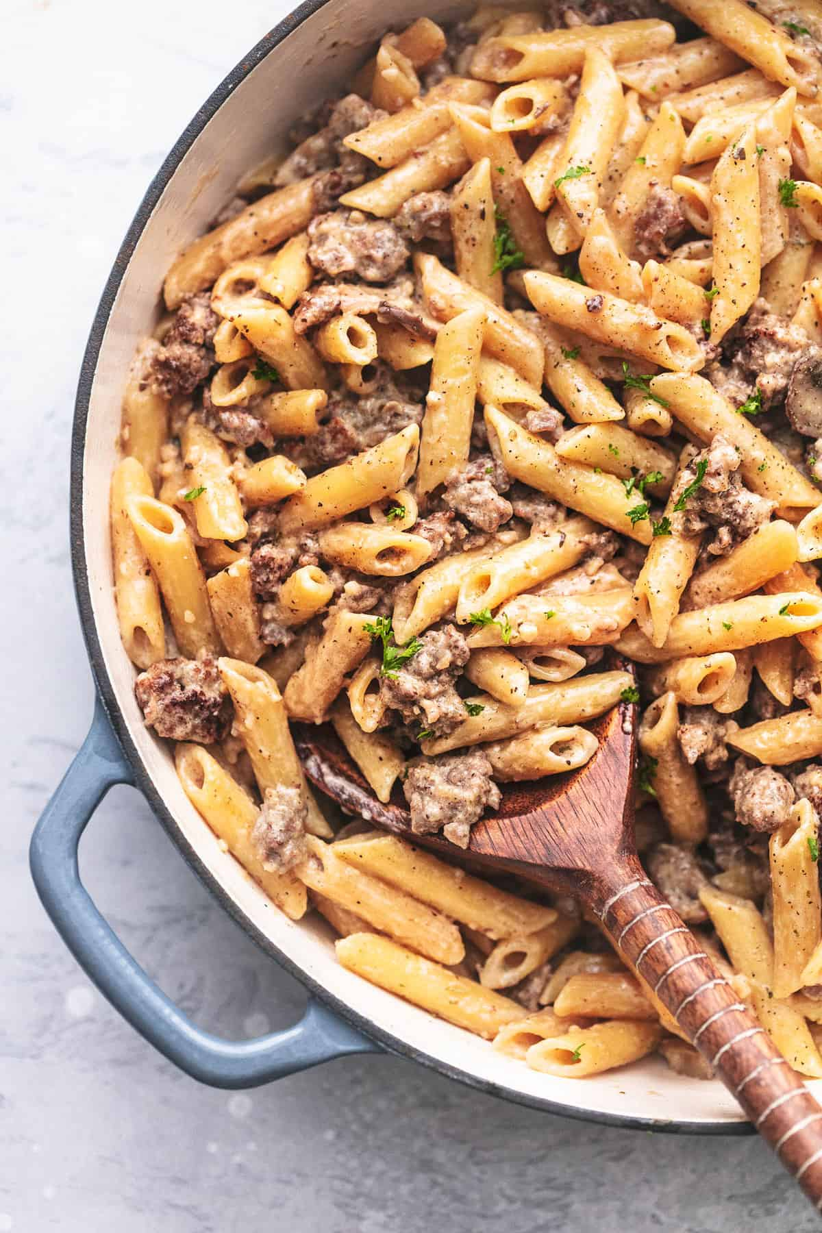 close up top view of creamy sausage and penne noodle pasta in a skillet with a wooden spoon.