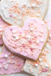 up close heart shaped sugar cookie with pink frosting and sprinkles