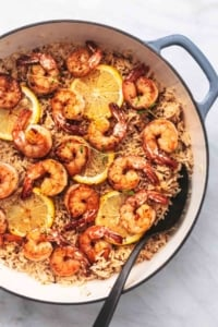 shrimp and rice with lemon slices in a skillet with a spoon