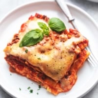 up close piece of lasagna topped with basil on a white plate with a fork
