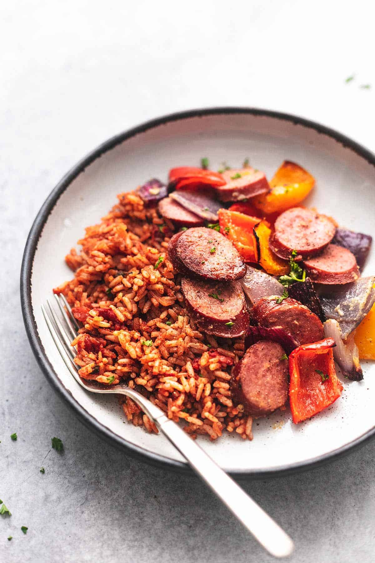 sausage and vegetables and rice on a plate with a fork