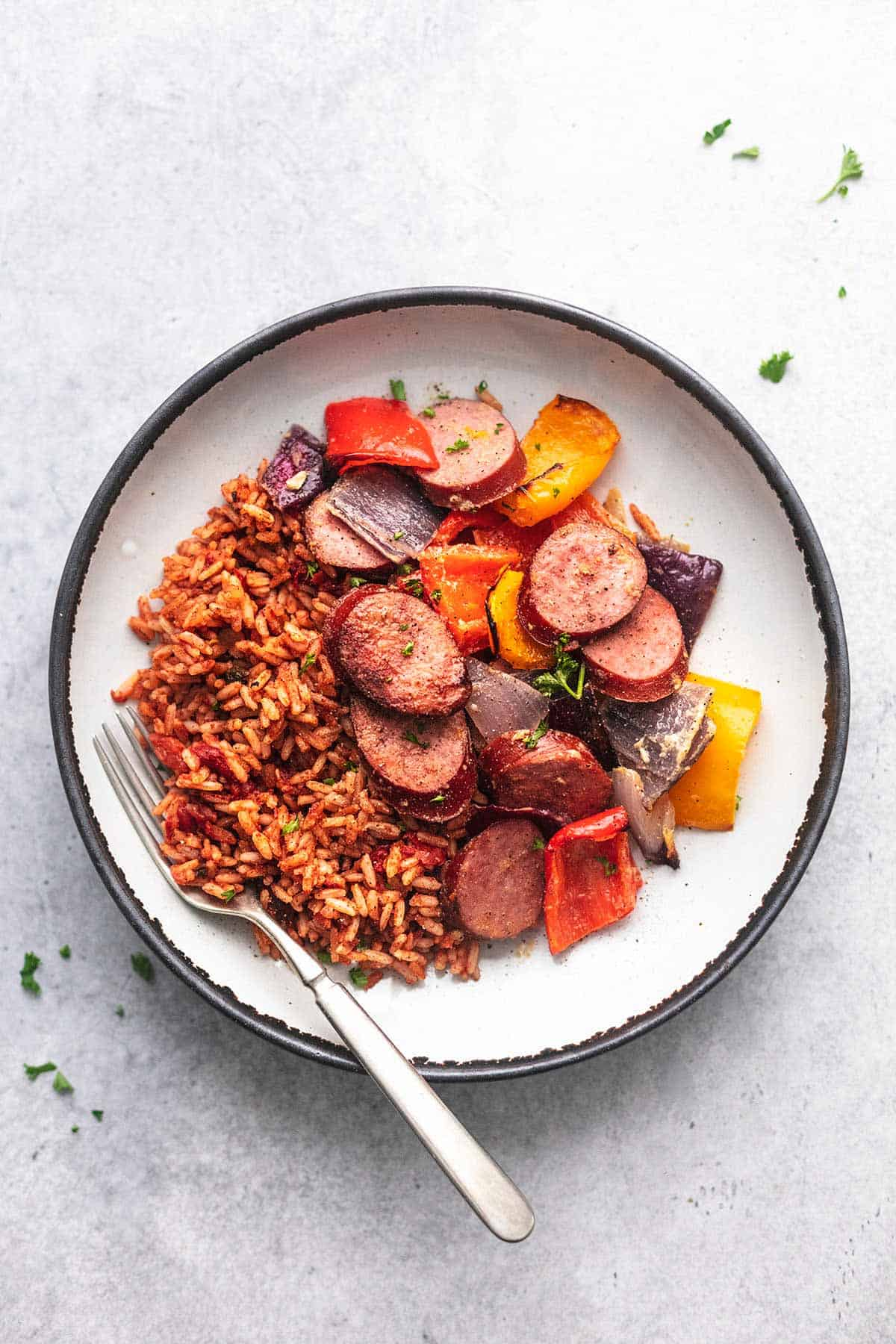 birdseye view of sausage vegetables and rice on a white plate with a fork