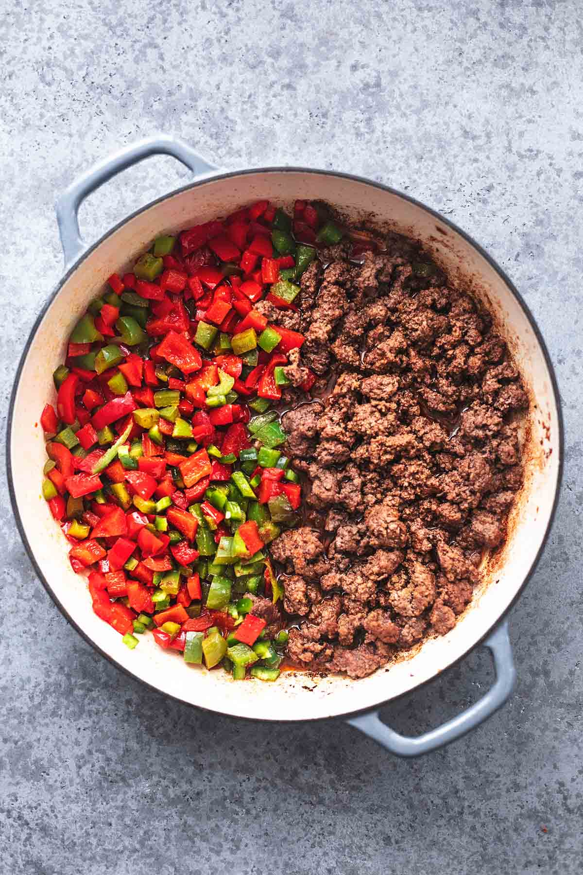 top view of ground beef and diced bell peppers in a skillet.