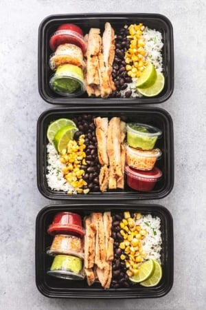 three chicken burrito bowls in meal prep containers
