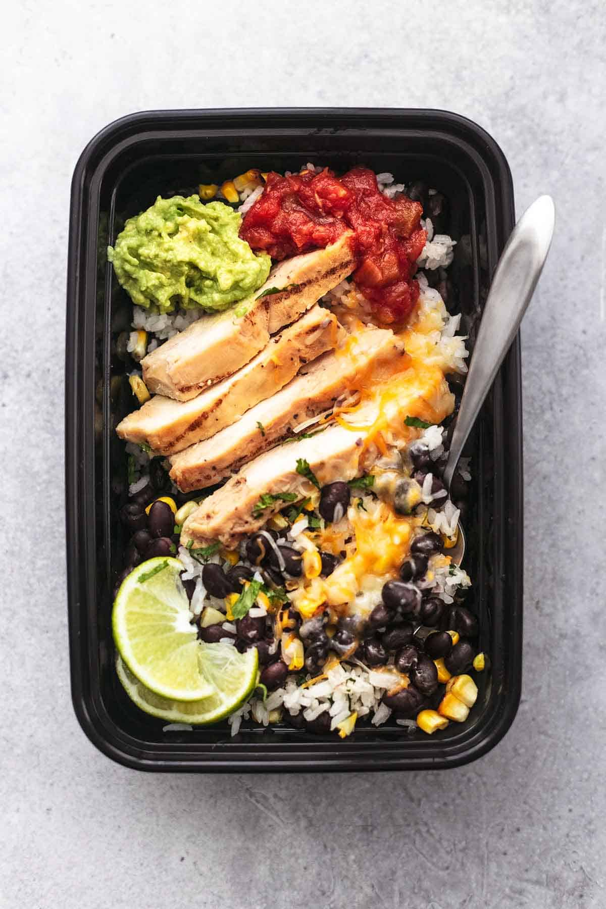 chicken, rice, beans, cheese, limes, guacamole, salsa in a meal prep container