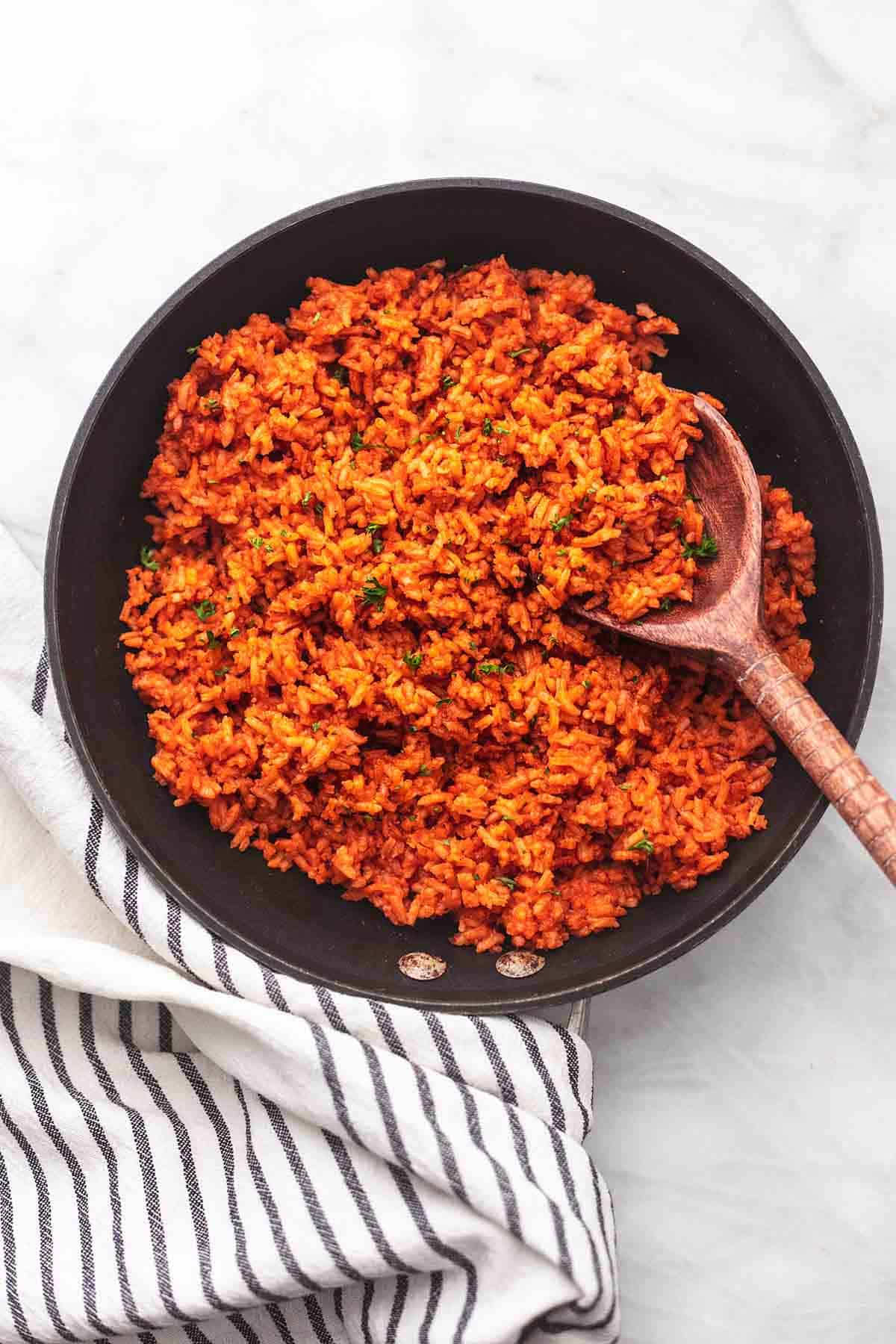 spanish rice in a skillet with a serving spoon