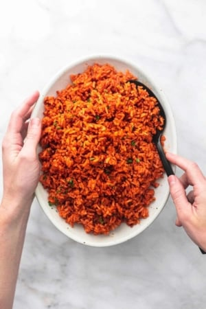 hands holding a plate with spanish rice
