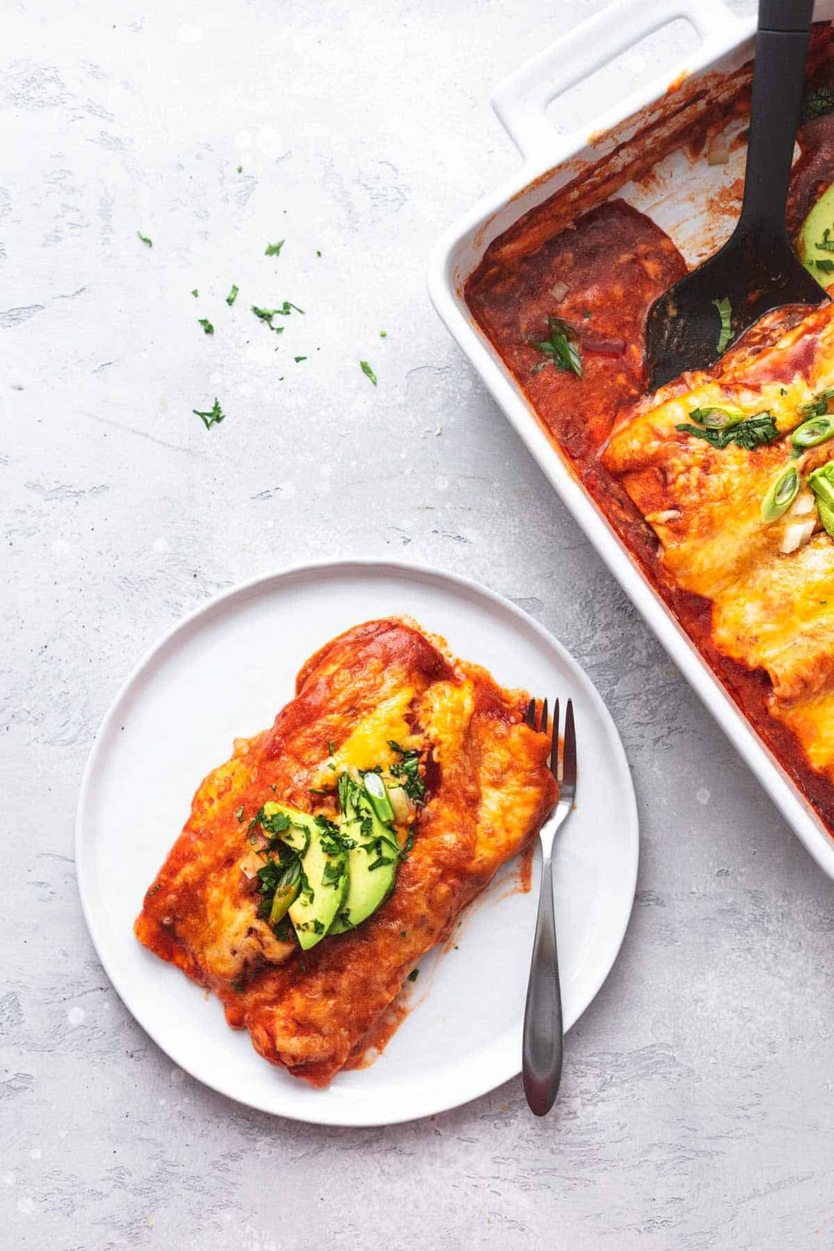 enchiladas on a plate next to a pan of enchiladas