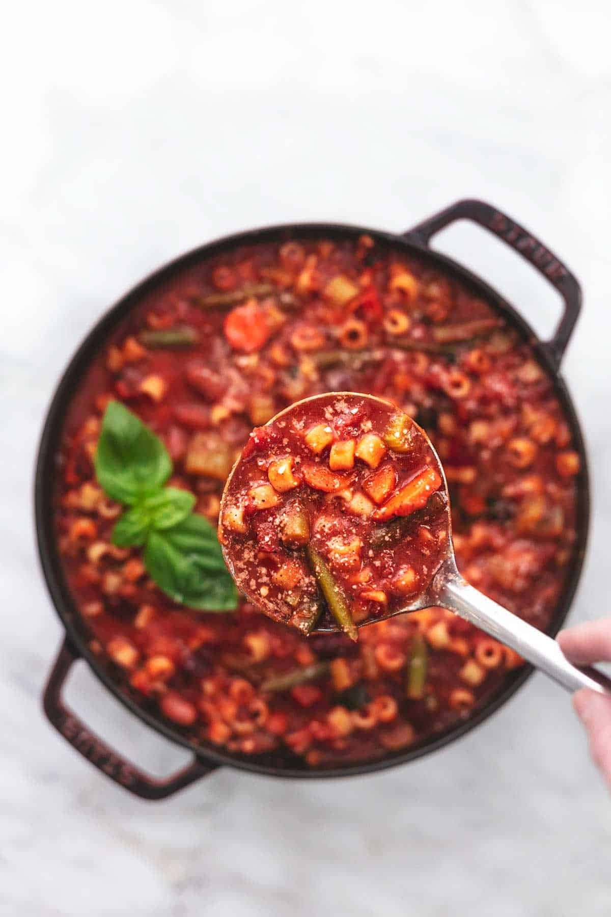 ladle full of minestrone soup over a pot of soup