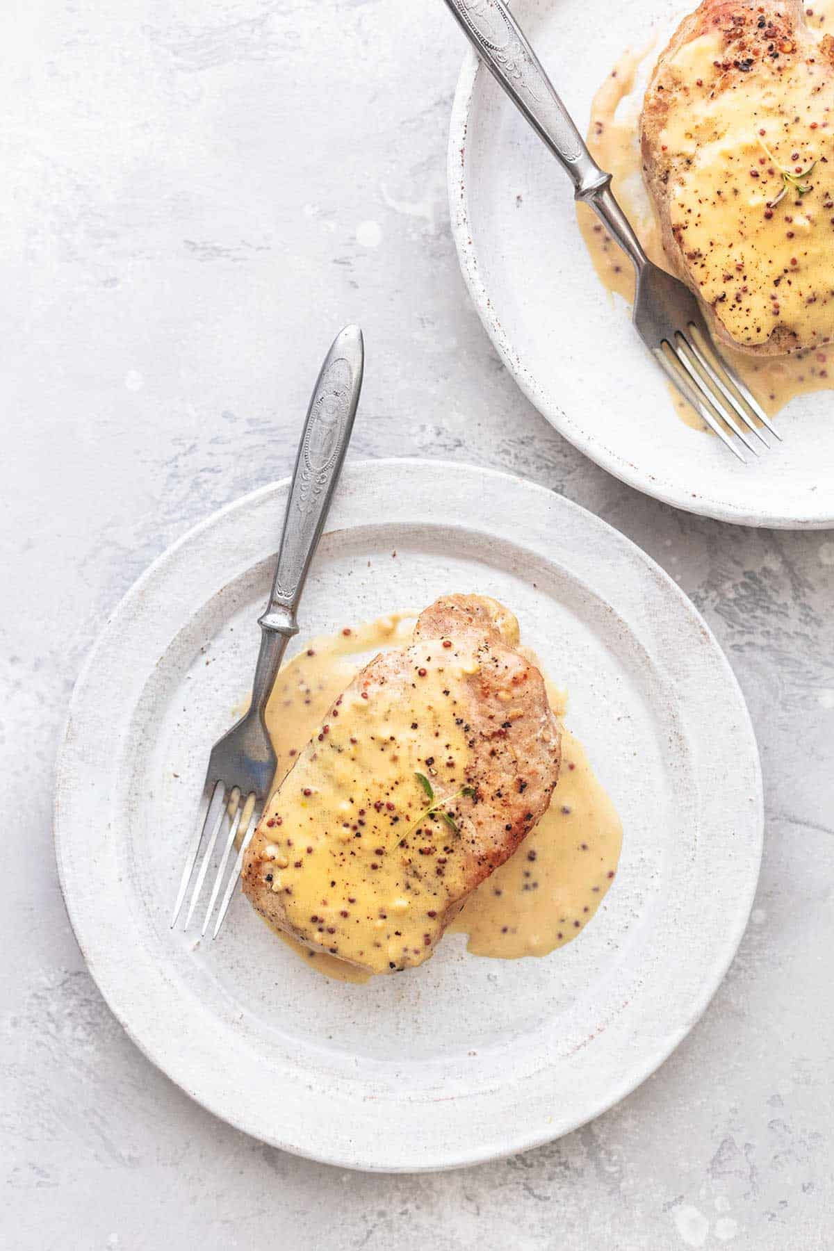 pork chops with cream sauce on white plates