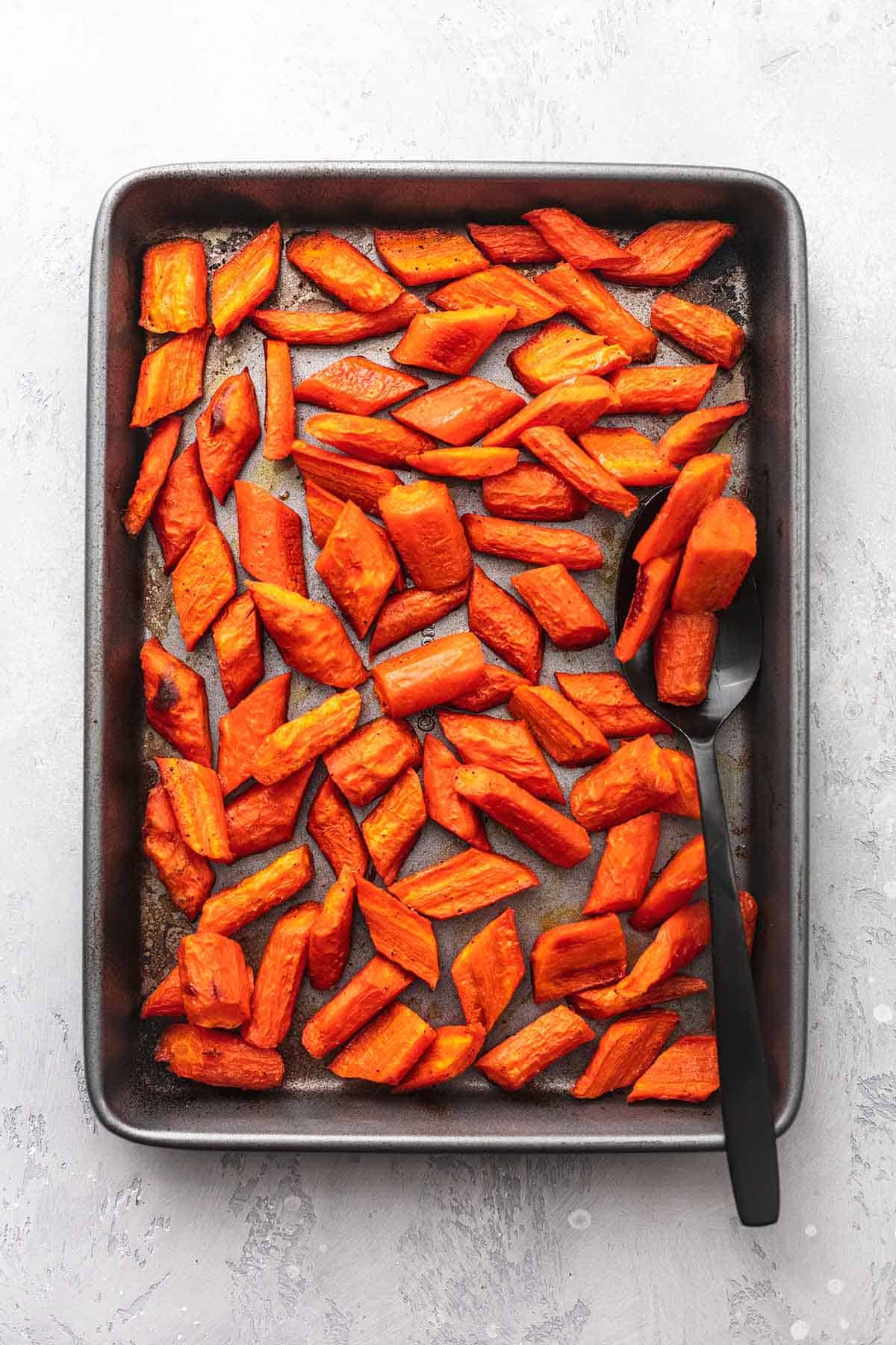 top view of roasted honey garlic glazed carrots with a serving spoon on a sheet pan.