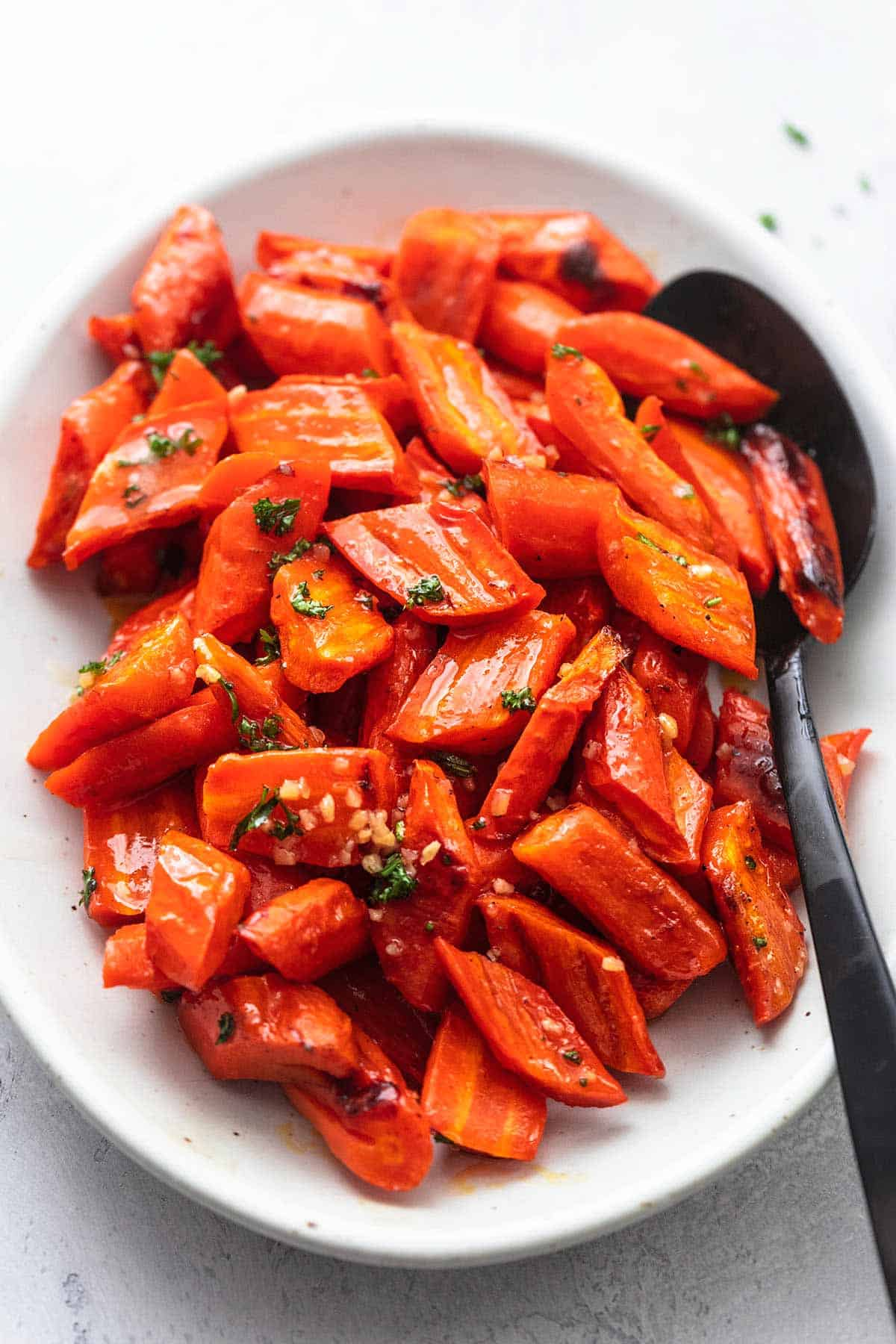 roasted honey garlic glazed carrots on a platter with a serving spoon.