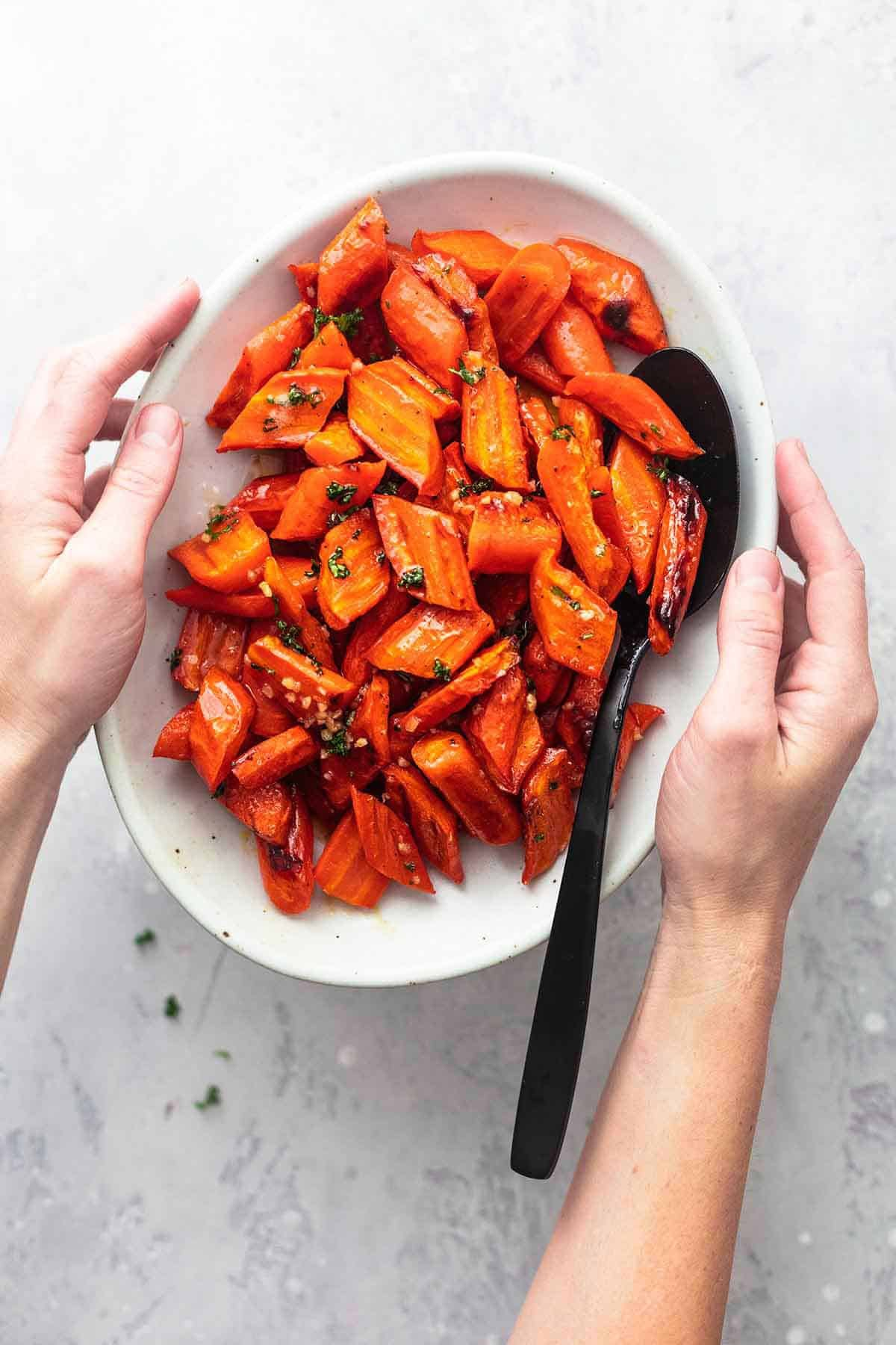 hands holding a platter of roasted carrots