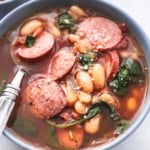 up close white bean and sausage soup with spinach