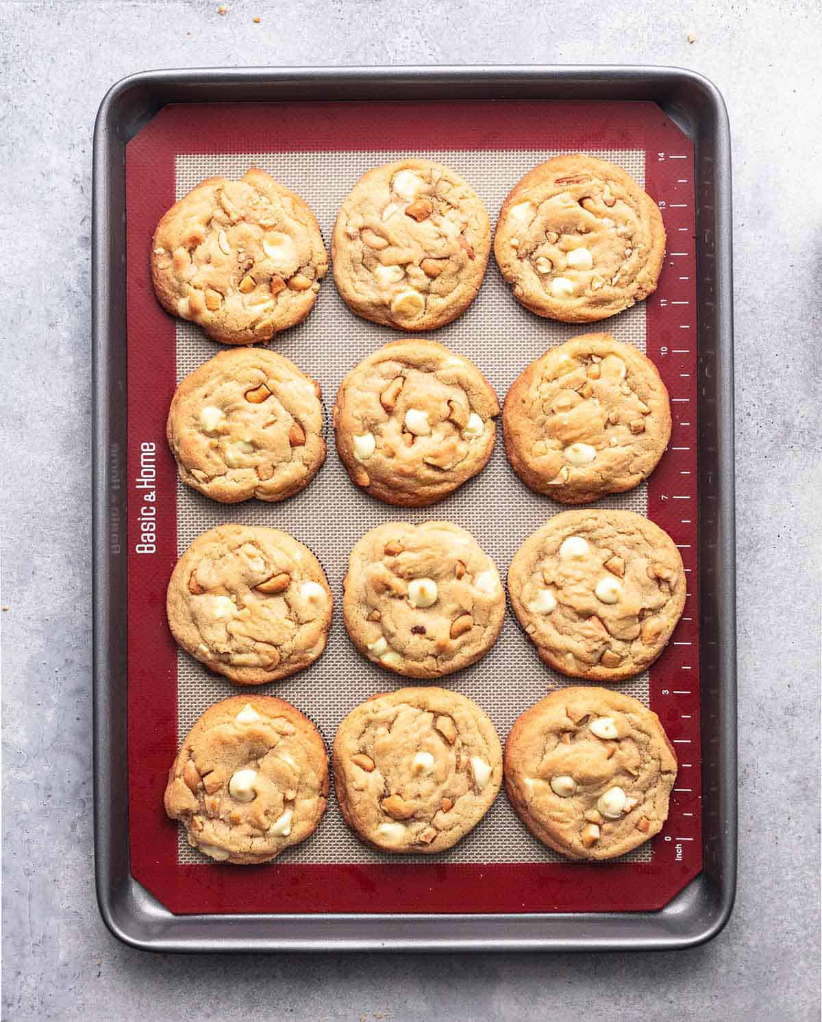 top view of chewy white chocolate cashew cookie on a baking sheet.
