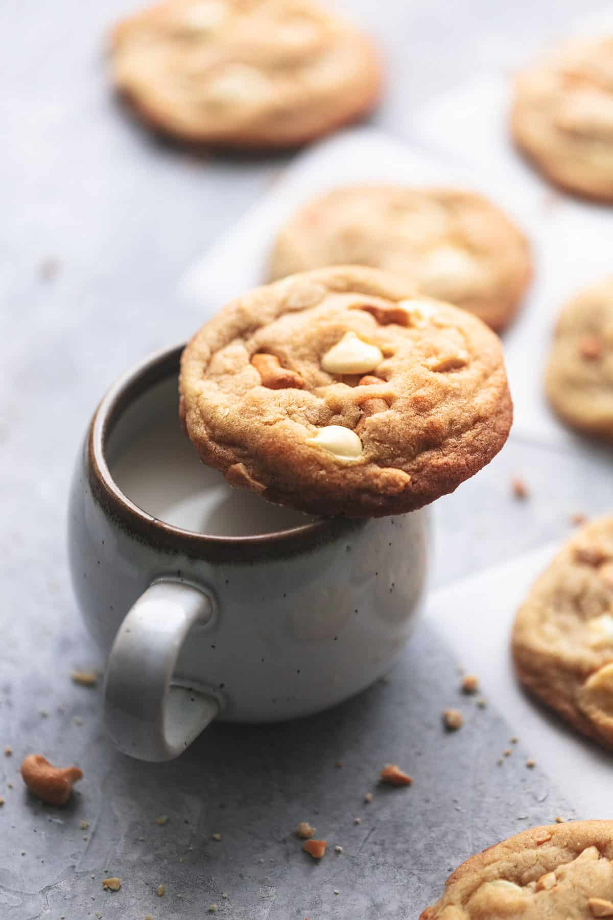 a chewy white chocolate cashew cookie a mug of milk with more cookies on the side.