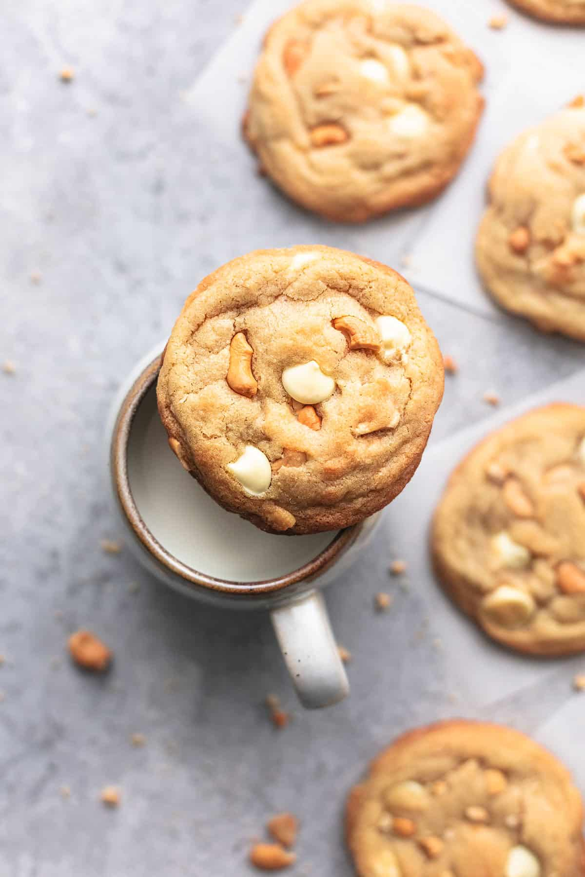 top view of a chewy white chocolate cashew cookie on a mug of milk with more cookies on the side.