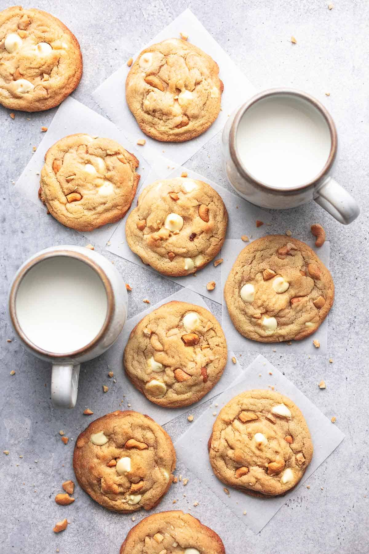 top view of chewy white chocolate cashew cookies with two mugs of milk on the side.