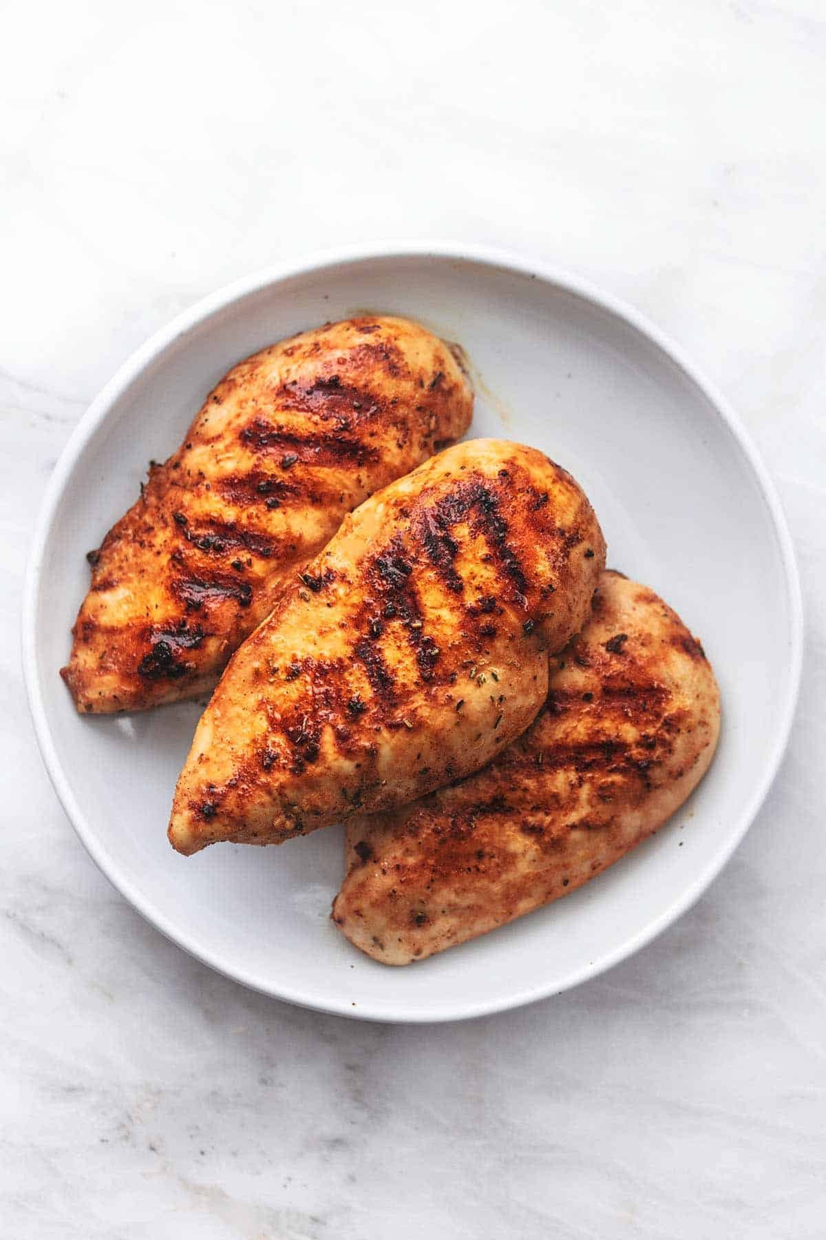 grilled chicken breasts on a white plate