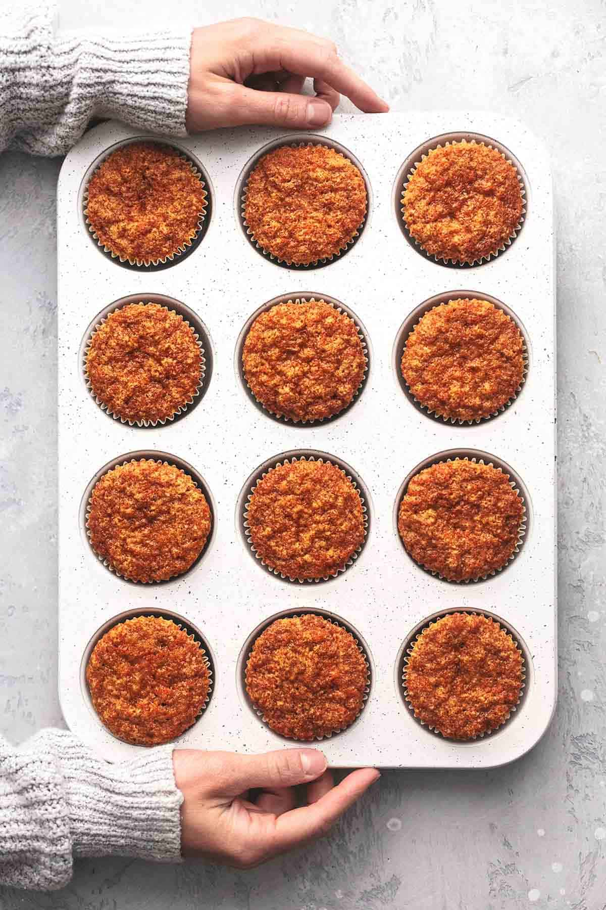 hands holding muffin tin with carrot muffins