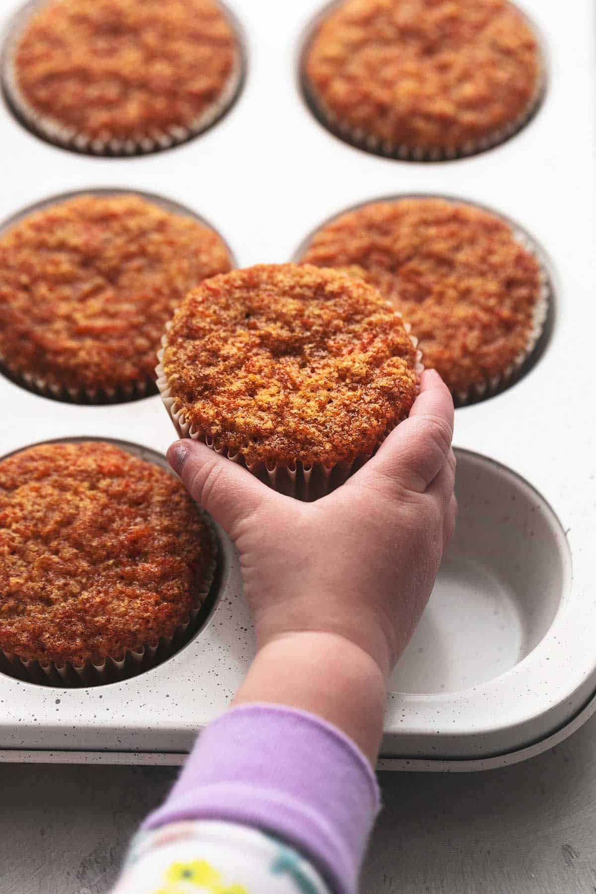 child's hand holding carrot muffin