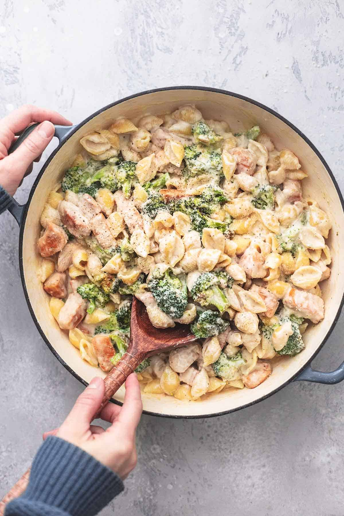 hands dishing spoonful of chicken and broccoli pasta