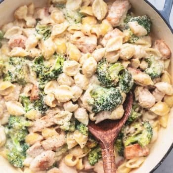 chicken alfredo pasta shells with broccoli and serving spoon in skillet
