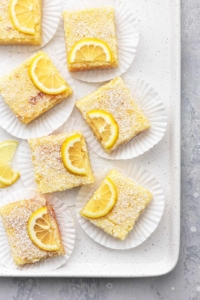 lemon bars on cupcake liners on a baking sheet overhead