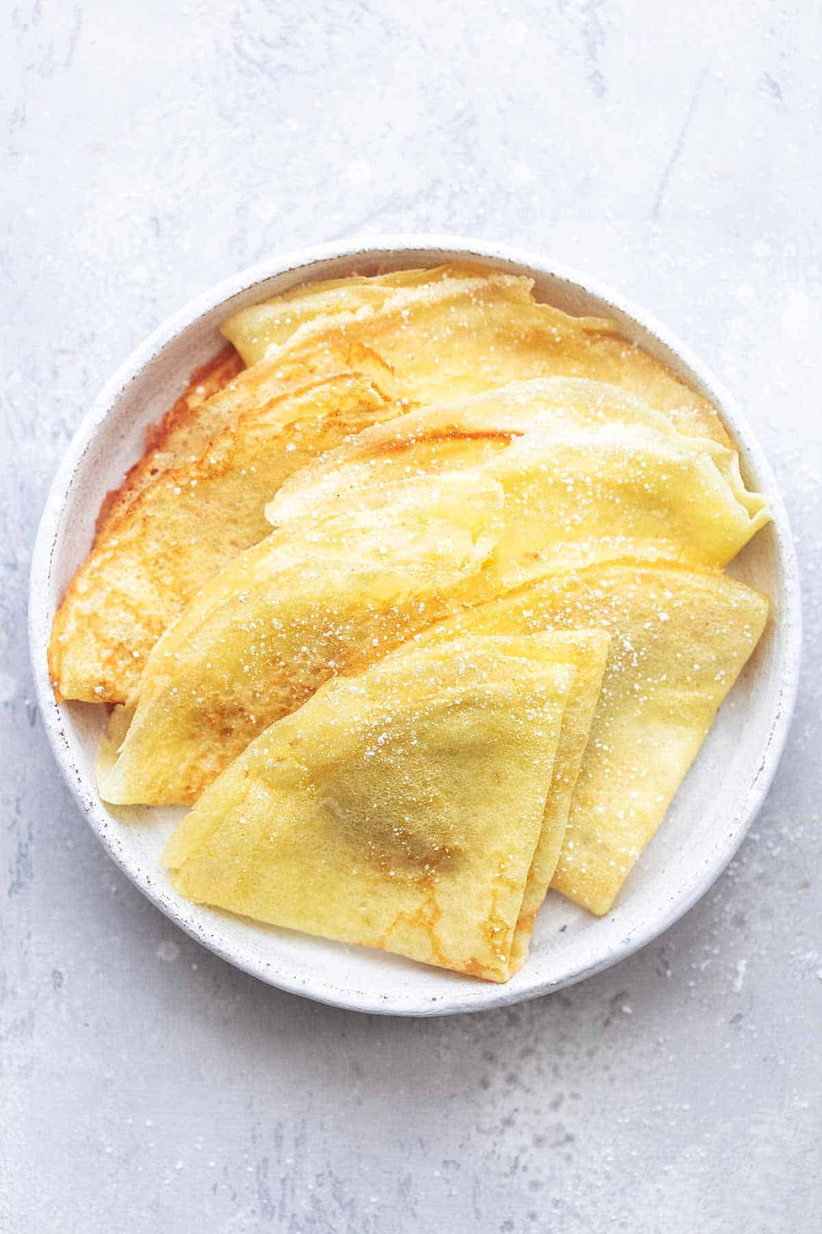 top view of folded crepes on a white plate.