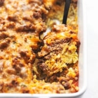 up close egg and hashbrown and sausage breakfast casserole in a white baking dish with a serving spoon