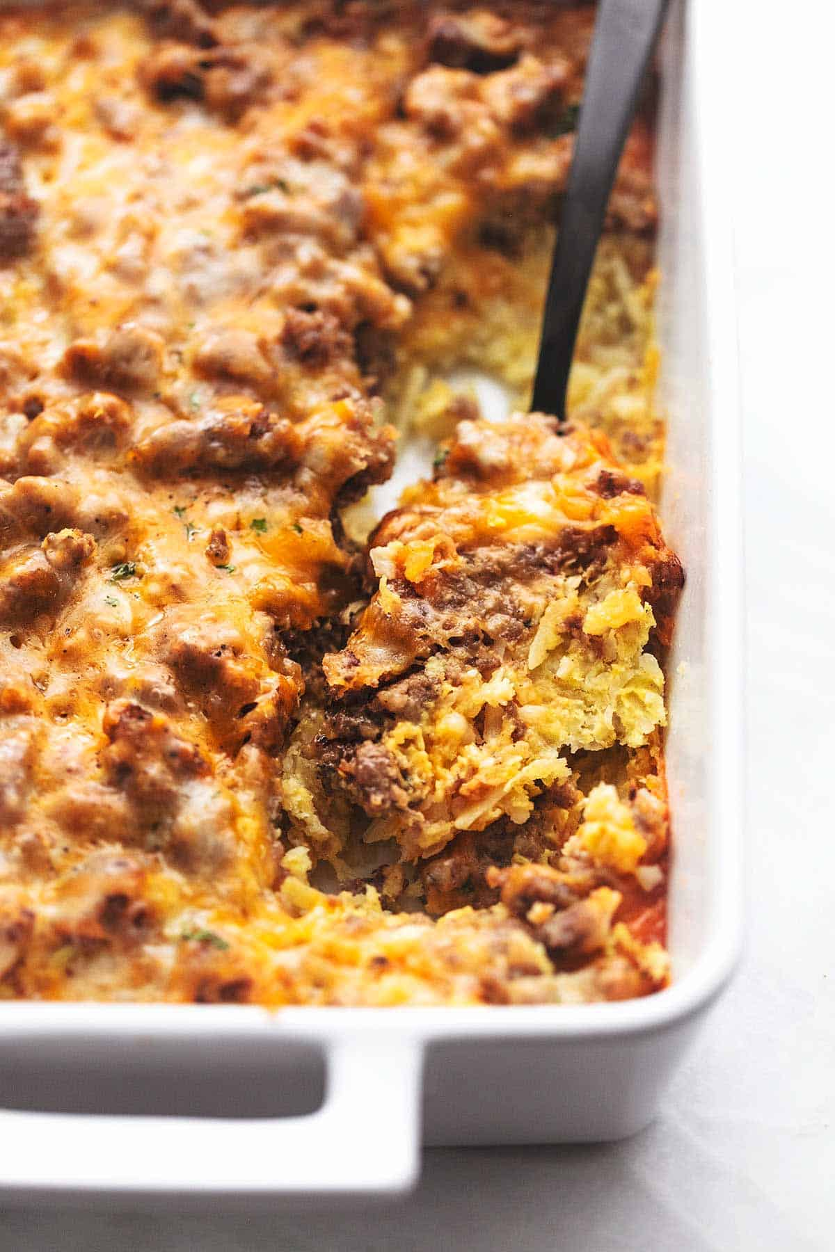 up close egg and hashbrown and sausage breakfast casserole in a white <a href=