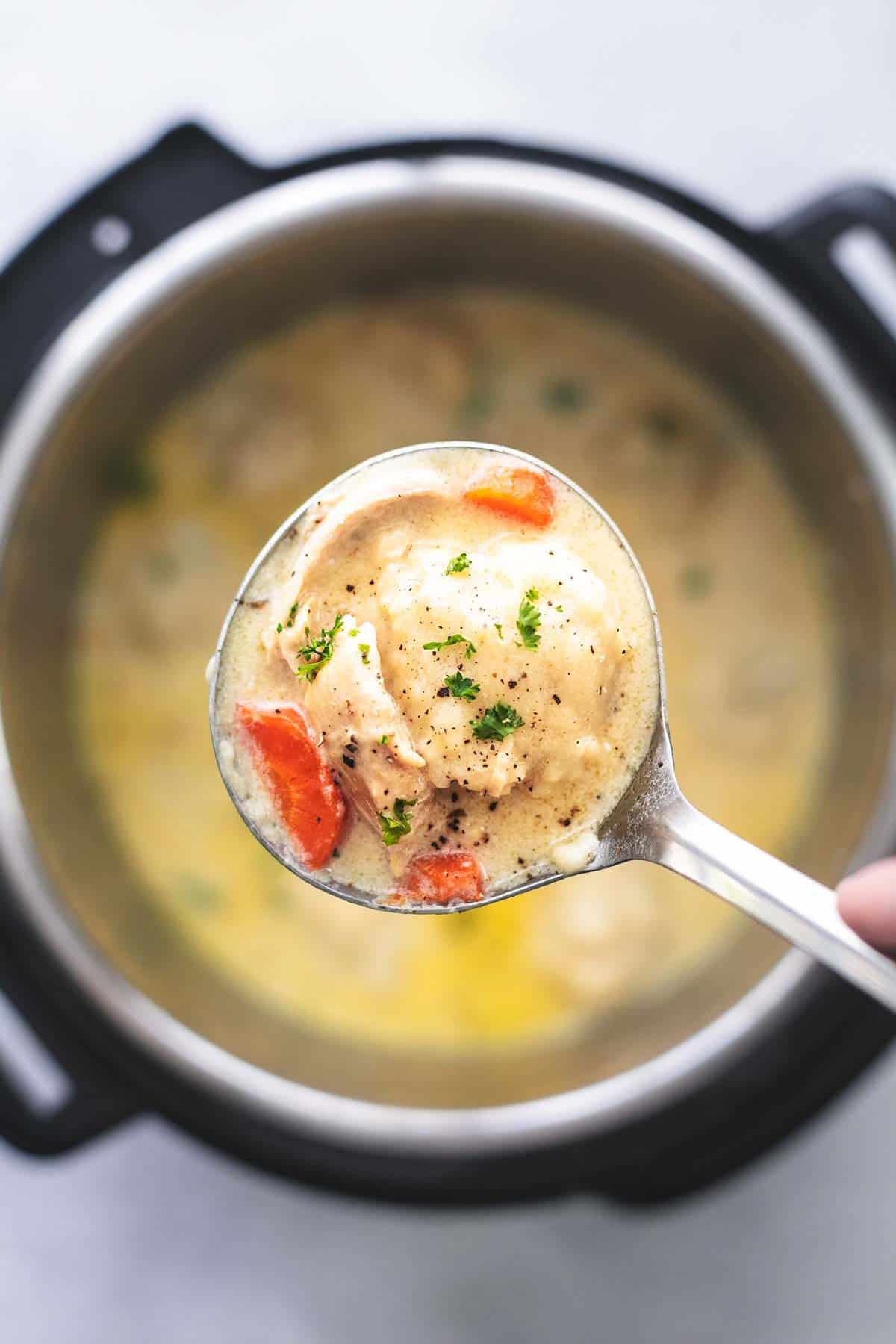 overhead ladle full of chicken and dumplings over pressure cooker