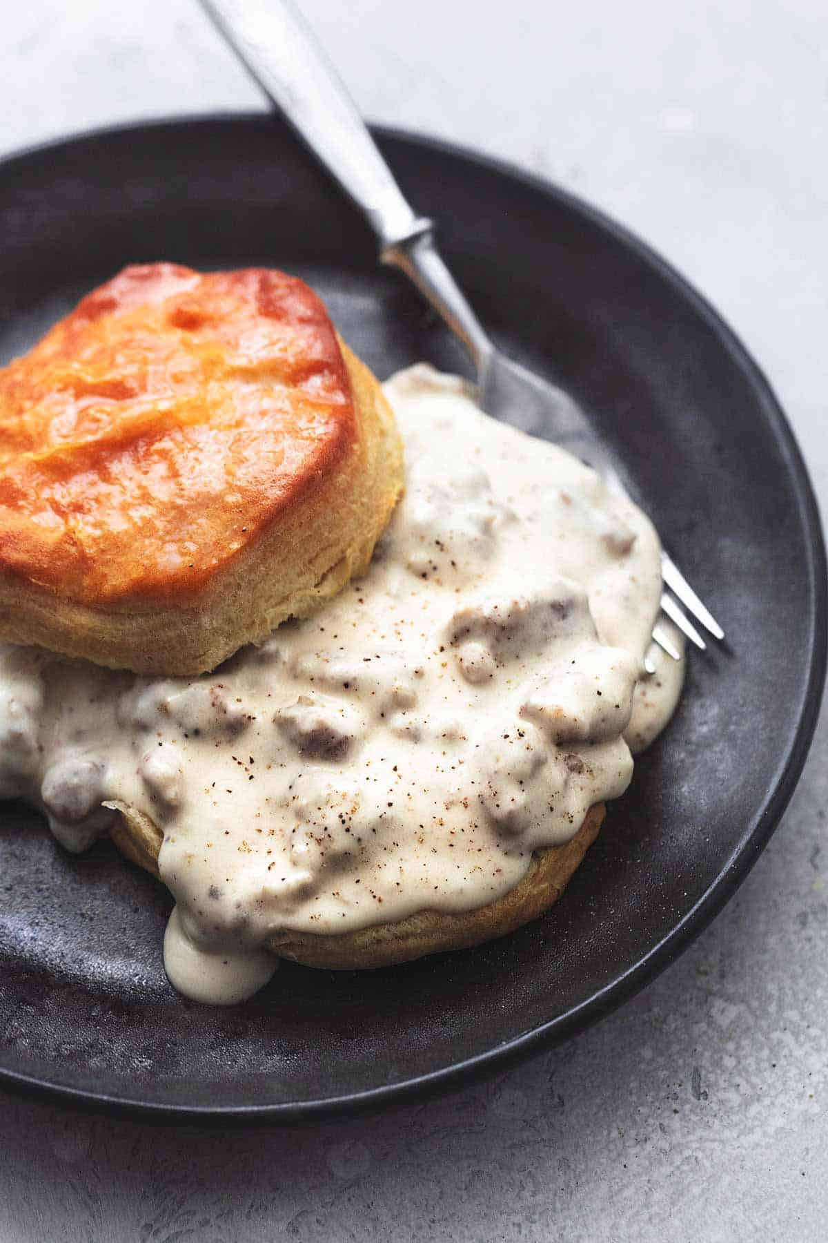biscuits and sausage gravy with fork on plate