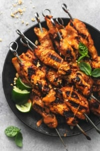 chicken skewers with limes on a black plate