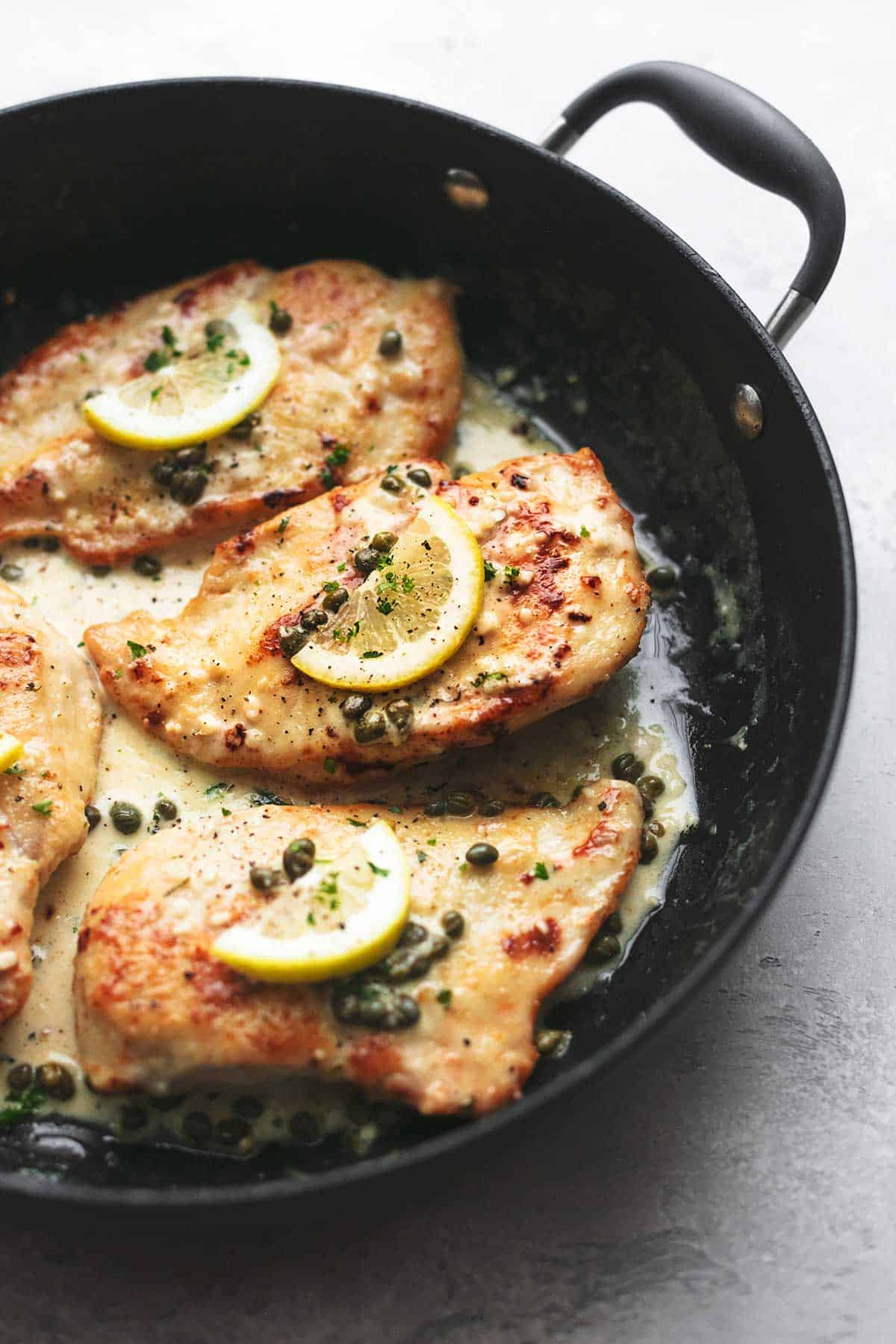 close up of creamy lemon chicken piccata in a skillet.