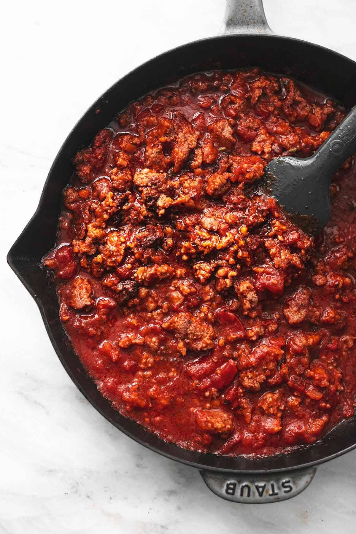 overhead cooked sausage in tomato sauce in skillet