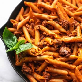 penne noodles with fresh basil and tomato sauce in skillet