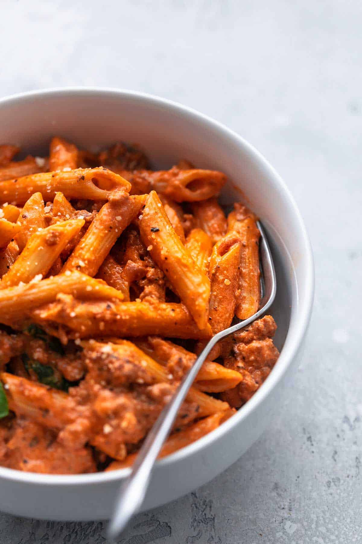 up close penne in tomato sauce in bowl with fork